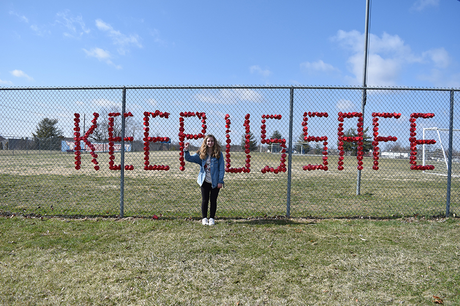 """Sophomore Sabrina Bohn stands in front of the fence facing Clayton Road after decorating it with the phrase """"Keep Us Safe"""" written in solo cups. Sophomores Lydia Harter, Carly Anderson and Emma Caplinger helped Bohn decorate the fence. """"It is so important for young people to make sure their voices are heard,"""" Caplinger said. """"The cups are to make sure that the issue is remembered past the day of the walkout, and so the community can hear our voices too."""""""