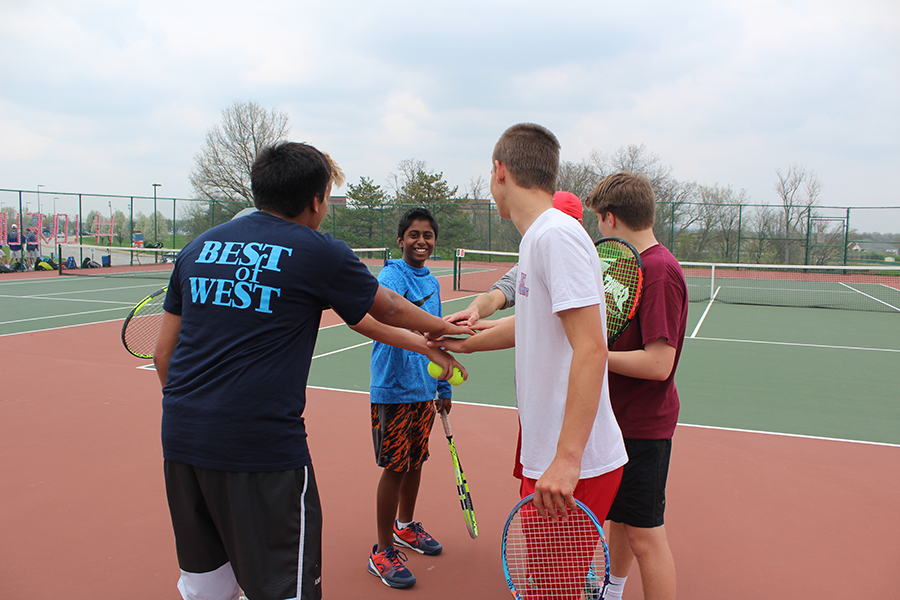 "Huddling up, members of the boys tennis team prepare to practice. ""On and off the court, tennis taught me how to persist, find my voice, and forge relationships,"" senior and captain Chris Nariskin said."