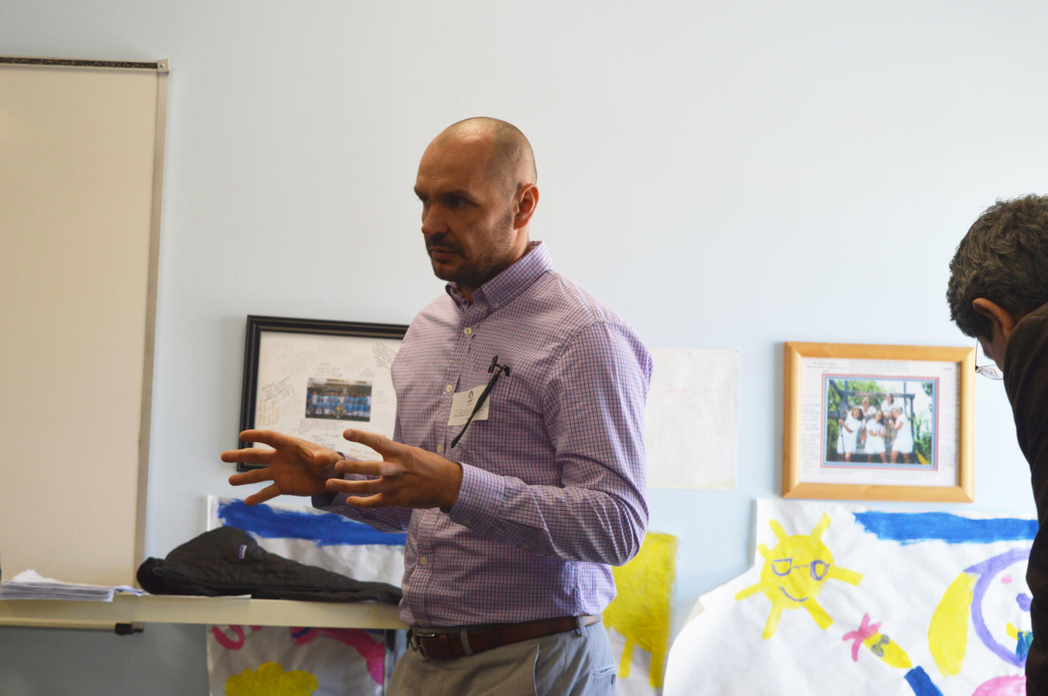 """Explaining history while describing his own culture, Dennis Nasufovic speaks to social studies teacher Jim Hermann's class. Nasufovic immigrated to St. Louis with his family in the 1990s where there is a current large Bosnian population. """"If you have a neighbor who is very loud watching the soccer game with a broken TV set outside, you know its a Bosnian whose team lost,"""" Nasufovic said."""
