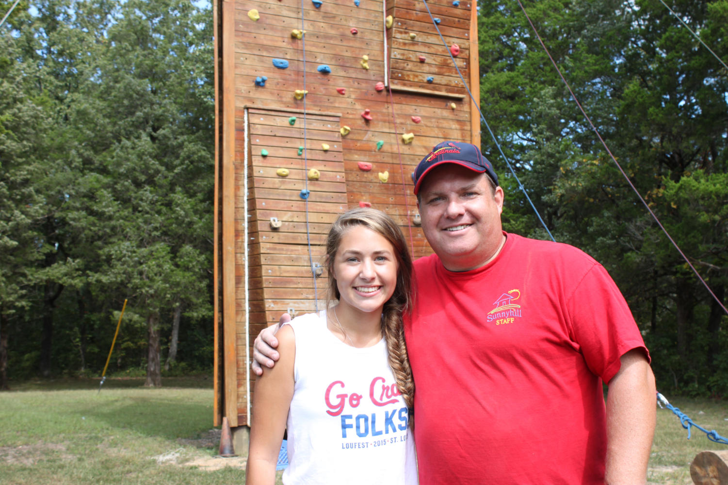 Posing with camp director Rob Darroch, senior Emily Rayfield stands in front of the climbing tower. Rayfield had been going to Sunnyhill Adventures since she was 7.
