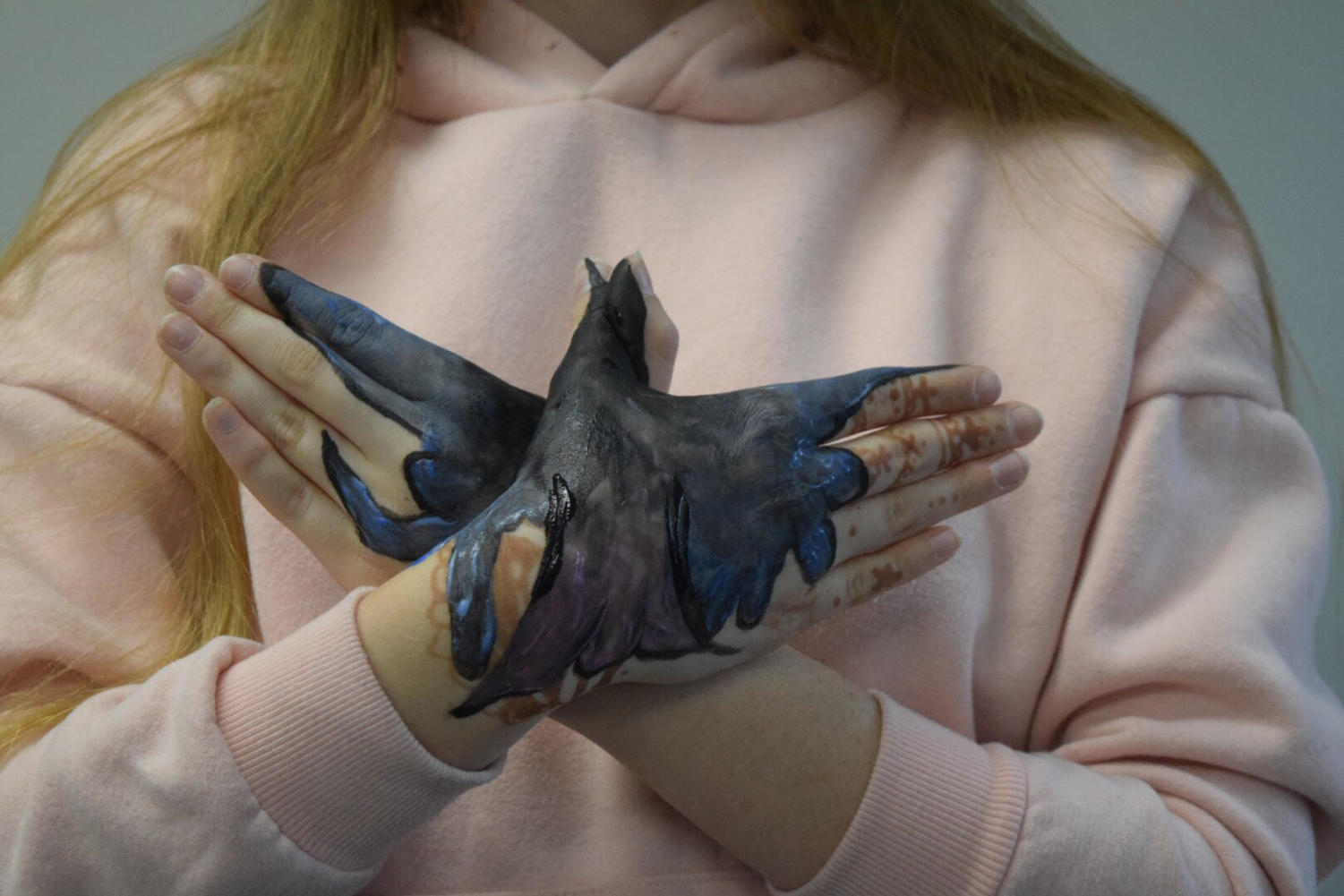 """Sophomore Ava Pfeil does a finger painting of a bird across her hands while signing the word bird in ASL. Students were required to sign an object, then paint it over their hands. """"I think it helped open my eyes and realize how hard it is for [deaf people] to communicate with others,"""" Pfeil said."""